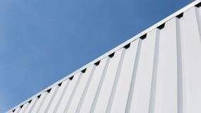 Metal la hoja blanca para el edificio industrial y la construcción en fondo del cielo azul Chapa del tejado o tejados acanalados Fotografía de archivo libre de regalías
