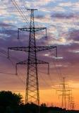 Metal la linea elettrica ad alta tensione del cuscinetto durante il tramonto o l'alba Fotografia Stock