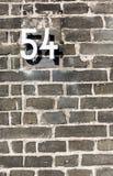 Metal la muestra del número de casa cincuenta y cuatro en la pared de ladrillo gris Fotos de archivo libres de regalías