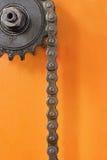 Metal la ruota dentata con la catena sul primo piano arancio del fondo Immagini Stock