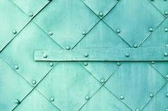 Metal la superficie verde chiaro di vecchi piatti di metallo martellati con i ribattini ed i dettagli architettonici su loro Fotografie Stock Libere da Diritti