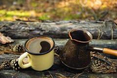 Metal la tasse avec du café chaud et le cezve sur le fond en bois avec les pièces de monnaie, les aiguilles et l'écorce de l'arbr Images libres de droits