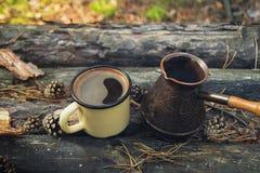 Metal la tasse avec du café chaud et le cezve sur le fond en bois avec les pièces de monnaie, les aiguilles et l'écorce de l'arbr Photographie stock