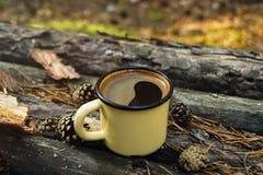 Metal la tasse avec du café chaud sur le fond en bois avec les pièces de monnaie, les aiguilles et l'écorce de l'arbre Photos libres de droits