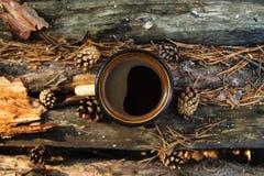 Metal la tasse avec du café chaud sur le fond en bois avec les pièces de monnaie, les aiguilles et l'écorce de l'arbre, vue supér Photo libre de droits