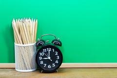 Metal la tazza delle matite con la sveglia sullo scrittorio su backgroun verde Fotografia Stock