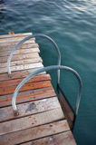 Metal Ladder. A metal ladder on a wooden pier to enter to the sea Stock Images