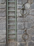 Metal ladder on old stone wall. Metal ladder and two rings mounted on the old stone wall of Prague waterfront royalty free stock photos