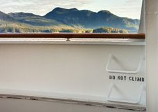Metal ladder rungs on cruise ship deck with view of mountain scenery in background ner Ketchikan, Alaska. Metal ladder rungs on cruise ship deck with words - do stock photos