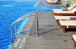 Metal ladder steps into the swimming pool Royalty Free Stock Image