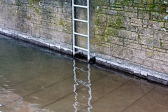 Metal ladder on stone wall at the river Stock Photo