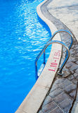 Metal ladder to exit from the swimming pool Stock Photos