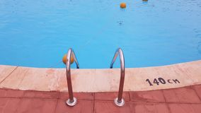 Railings ladder to the pool. Metal ladder to the pool. in the pool is clear blue water. water activities stock video