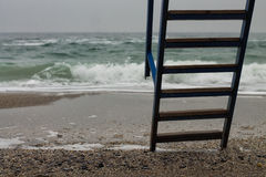 Metal ladder with wooden steps to sea Royalty Free Stock Image