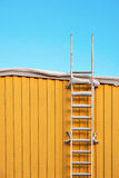 Metal ladder on yellow wall Stock Photography