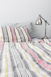 Metal lamp near bed with colorful bedclothes Royalty Free Stock Image