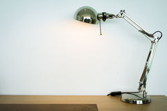 Metal lamp on the wooden desk Royalty Free Stock Image