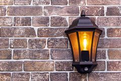 Metal lantern on a brick wall background. Stylish lamp in a metal frame royalty free stock images