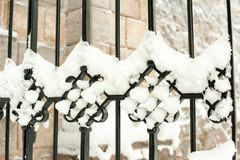 Metal las curvas negras ornamentales de la cerca cubiertas con nieve Imagen de archivo