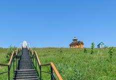 Metal las escaleras con las verjas que llevan al lugar del rezo y a una capilla de madera cerca de la pequeña casa en la colina Imágenes de archivo libres de regalías