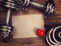 Metal las pesas de gimnasia y el corazón rojo en un fondo de madera Foto de archivo