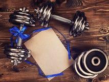 Metal las pesas de gimnasia y la cinta azul en un fondo de madera Fotos de archivo libres de regalías