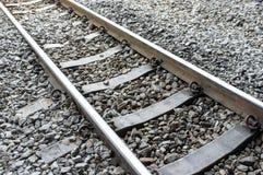 Metal las pistas ferroviarias y los durmientes con el fondo de piedra foto de archivo
