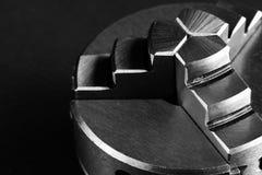 Metal lathe chuck. Stylized image of metal lathe 3-jaw chuck on black background Royalty Free Stock Photos