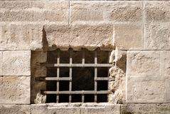 Metal lattice on a background of stone wall Royalty Free Stock Photo
