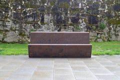 Metal le banc sur le fond d'un mur en pierre Photo stock