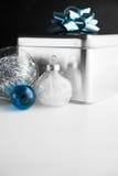 Metal le boîte-cadeau avec l'arc bleu et les babioles de Noël sur les milieux en bois blancs et noirs Photo libre de droits
