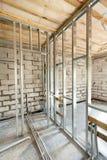 Metal le cadre de profil pour des murs et des tuyaux de plaque de plâtre avec des valves d'un système de chauffage dans la maison photo stock