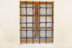 Metal le gril avec un modèle géométrique sur une vieille fenêtre en bois Images libres de droits