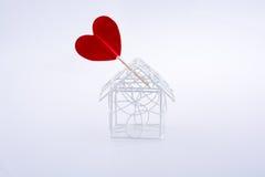 Metal le modèle de maison de câble et la forme rouge de coeur Photos stock