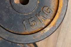 Metal le poids 15 kilogrammes avec la rouille pour le banc sur un backgroun en bois image libre de droits