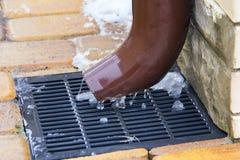 Metal le tuyau de descente d'eaux ménagères et une grille de tempête, concept de changement de saison Photos libres de droits