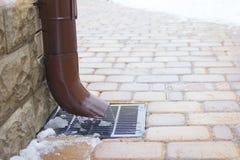 Metal le tuyau de descente d'eaux ménagères et une grille de tempête, concept de changement de saison Images libres de droits