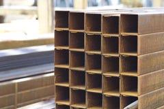 Metal le tuyau de profil de la section transversale rectangulaire dans les paquets à l'entrepôt des produits métalliques image libre de droits