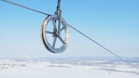 Metal leading ring and electrical wire against sky. Closeup grey metal leading ring turns and moves electrical wire in air against clear blue sky stock footage