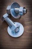 Metal les écrous et les screwbolts de construction de joints de boulon sur la BO en bois Image stock