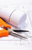 Metal les pinces et le diagramme électrique roulé sur le dessin de construction de la maison Photographie stock libre de droits