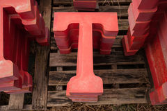 Metal letter T. Stacks of three diminutional red metal letter T sign for sale at store Stock Photos