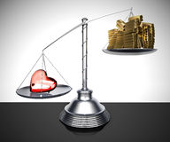 Metal libra with a glass heart and gold bars. Balance with the weight of the glass heart that exceeds that of many gold ingots Royalty Free Stock Photography