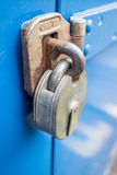 Metal Lock. A rusted lock on a blue background Royalty Free Stock Photography