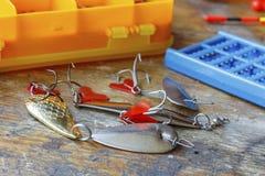 Metal los cebos de pesca con los accesorios en una tabla de madera Imagenes de archivo