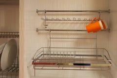 Metal los estantes para los platos en las verjas, armarios de cocina incorporados foto de archivo libre de regalías