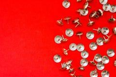 Metal los pernos o los thumbtracks agudos brillantes dispersados en fondo rojo con el área limpia de la foto para las etiquetas o fotos de archivo libres de regalías