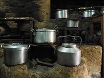 Metal los platos, potes de aluminio enormes y las cálices se colocan en desorden en un horno de la arcilla en una casa del pueblo Imagen de archivo libre de regalías