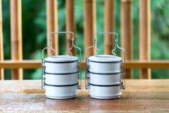 Metal los portadores de la comida en una tabla de madera, un contexto de bambú Fotografía de archivo