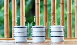 Metal los portadores de la comida en una tabla de madera, un contexto de bambú Imagen de archivo libre de regalías